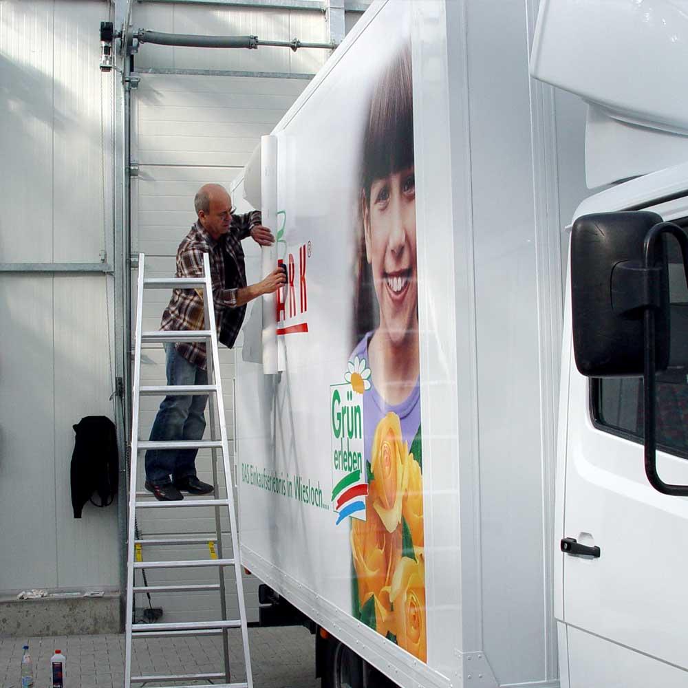 Montage der seitlichen Fahrzeugbeschriftung auf dem LKW